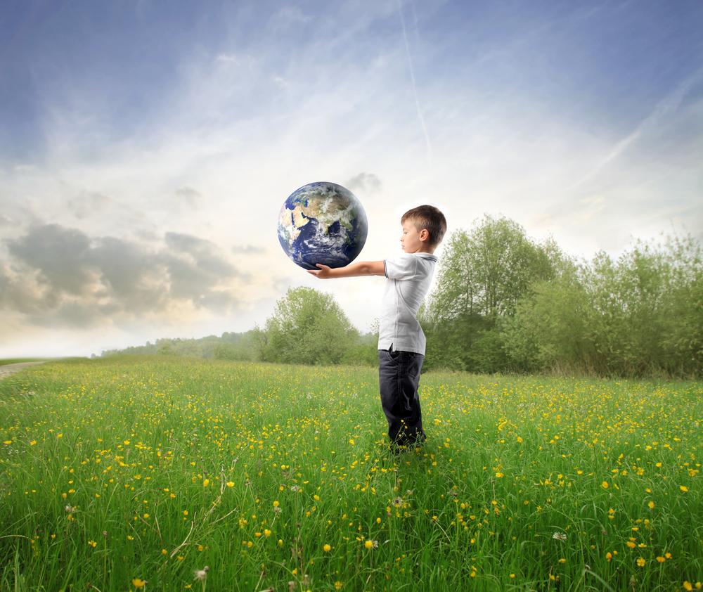 Niño en el campo con el planeta Tierra en sus manos